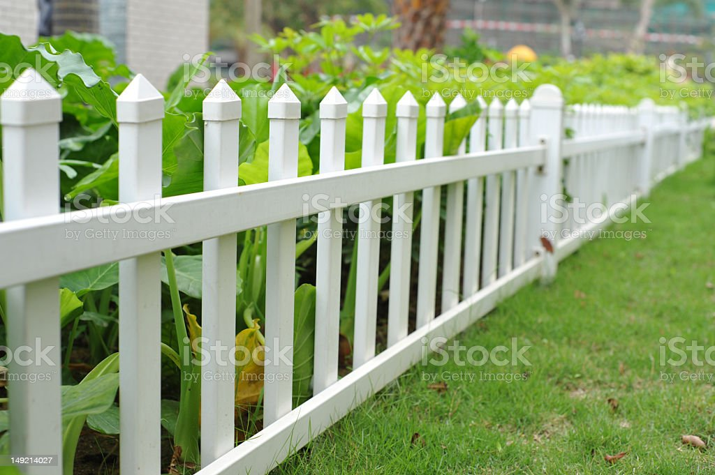 White picket fence featuring green grass royalty-free stock photo