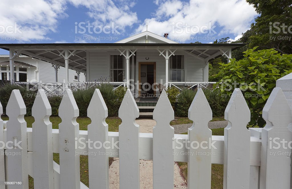 White Picket Fence in front of Detached House stock photo