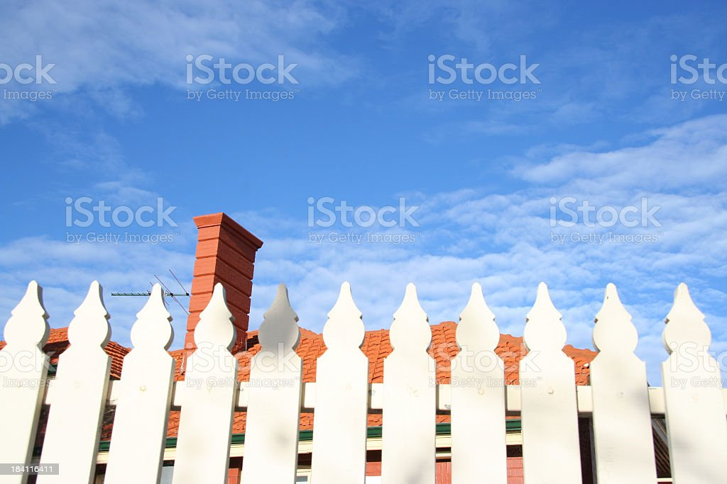 A white picket fence with a blue sky in the background royalty-free stock photo
