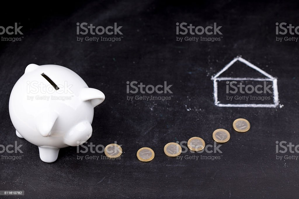 White piggy bank on blackboard: saving for a house stock photo