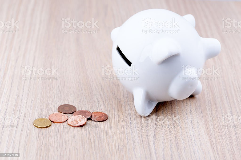 White piggy bank on its side on a wooden desk stock photo