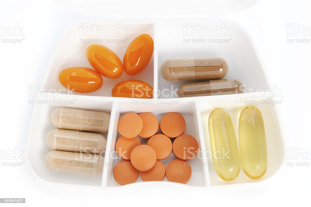 White pill box organizer dispencer with colorful drugs isolated royalty-free stock photo