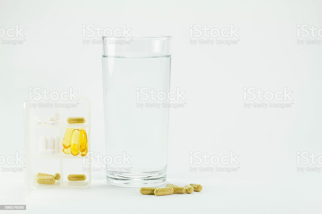 White pill box with pills, glass of water and pills stock photo