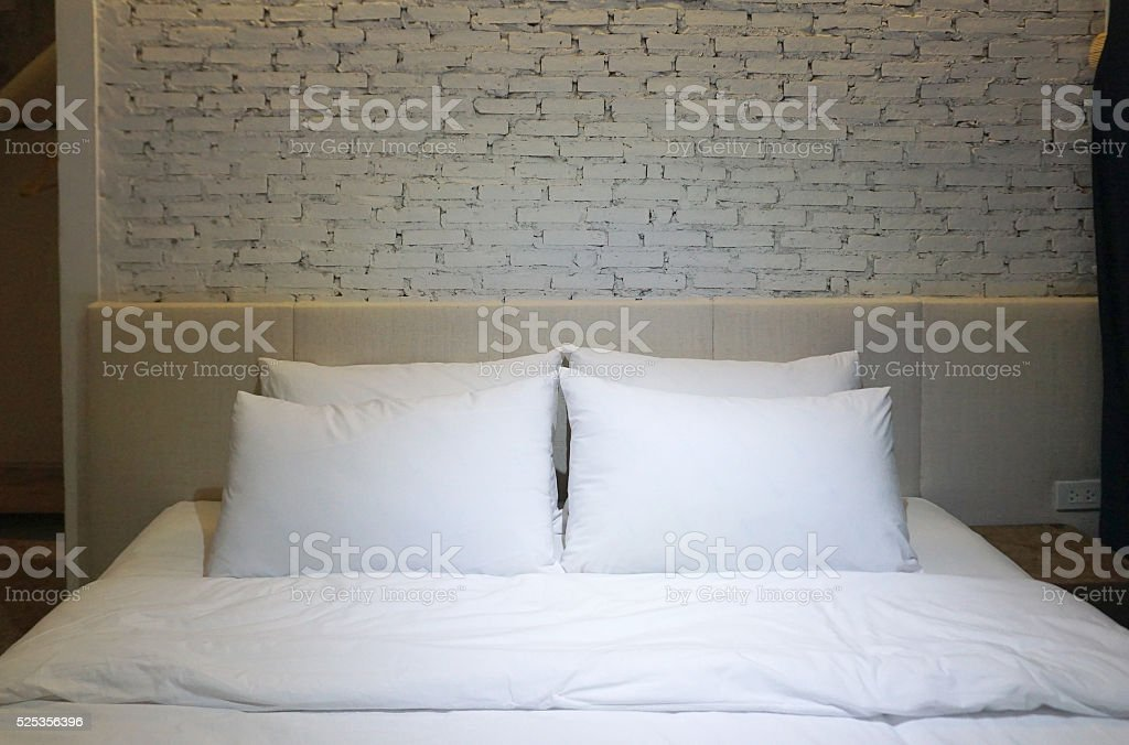 White pillow and bedsheet with focus lighting in the middle stock photo