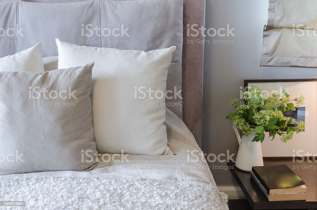 white pillows on white bed with vase of plant stock photo