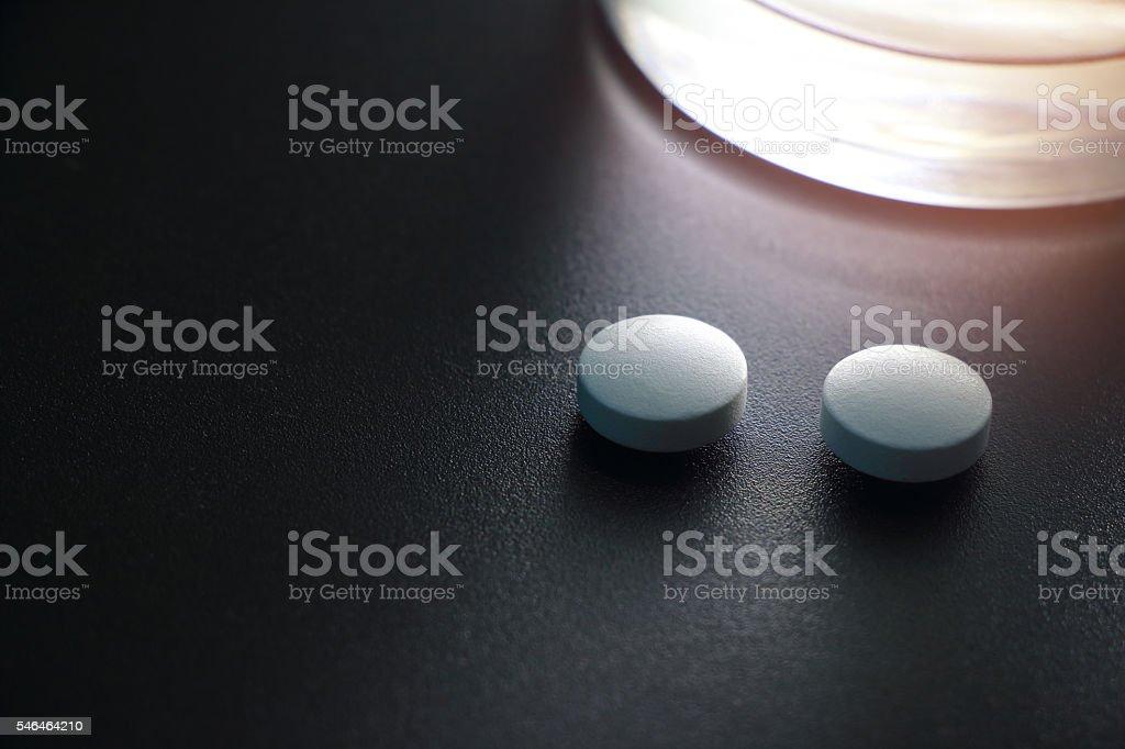 white pills on black background, insomnia stock photo
