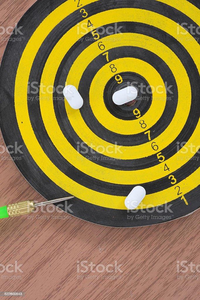 White pills on yellow and black dart target stock photo