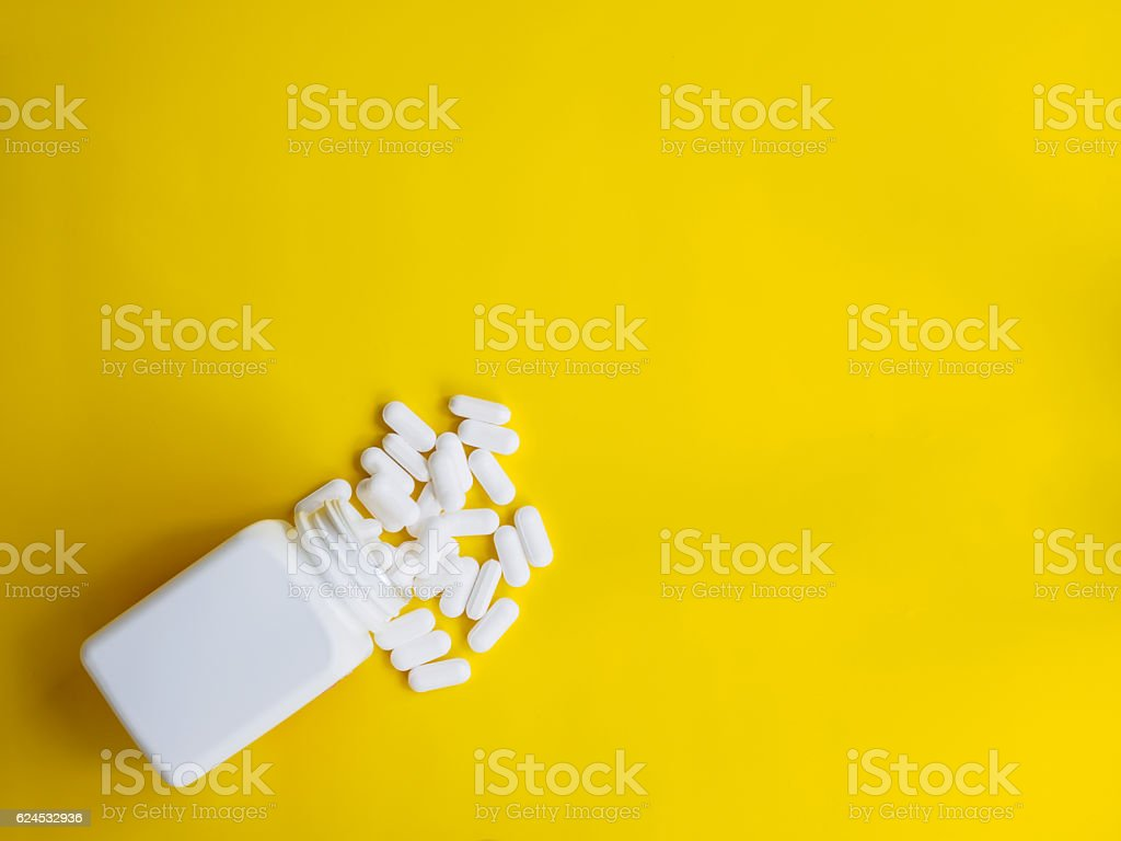 white pills spill out white bottle on yellow background stock photo