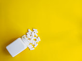 white pills spill out white bottle on yellow background