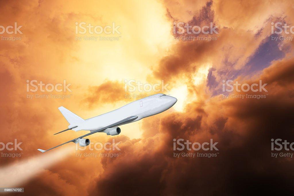 White plane jet engine flying through golden cloud on sky stock photo