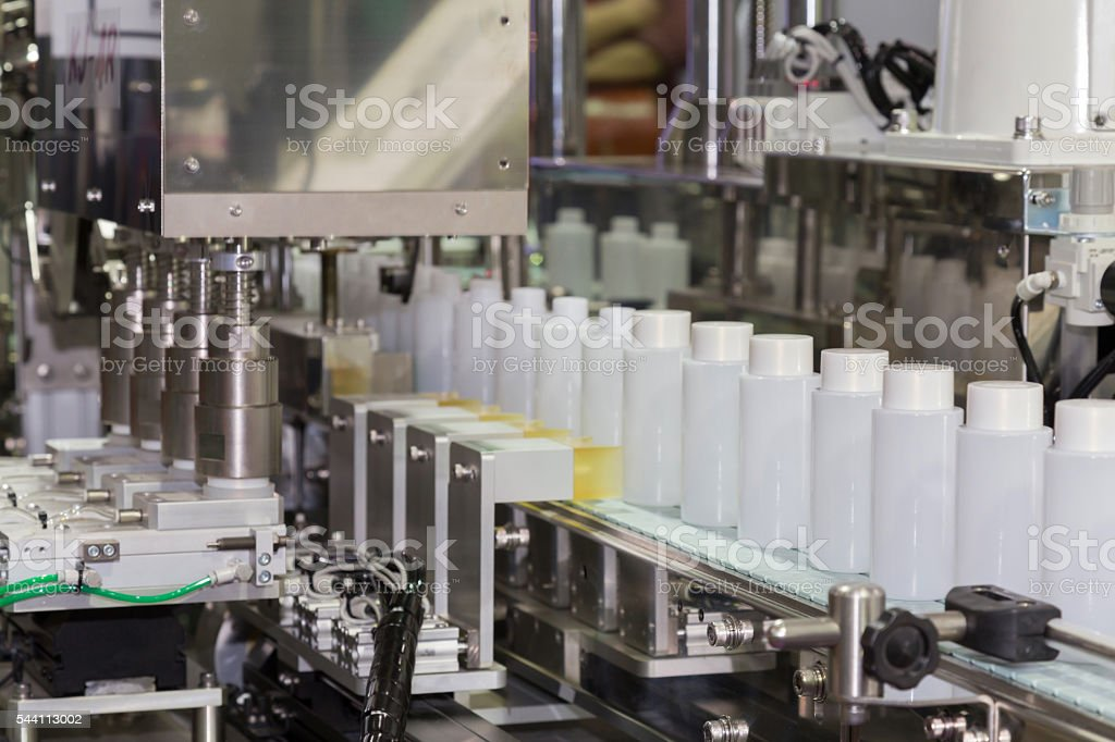 white plastic bottle on factory line machine in the factory, stock photo