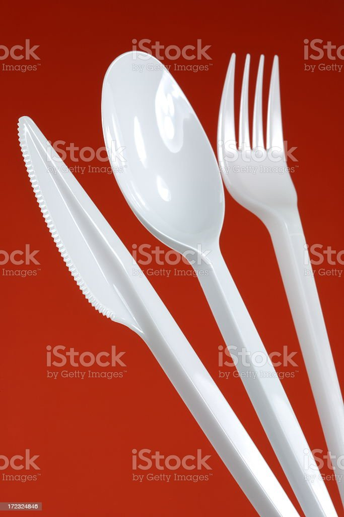 White plastic cutlery on a red background stock photo