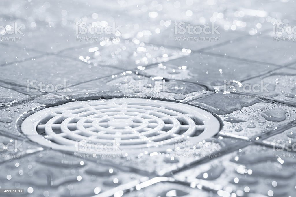 White plastic shower drain with drops of water around it stock photo