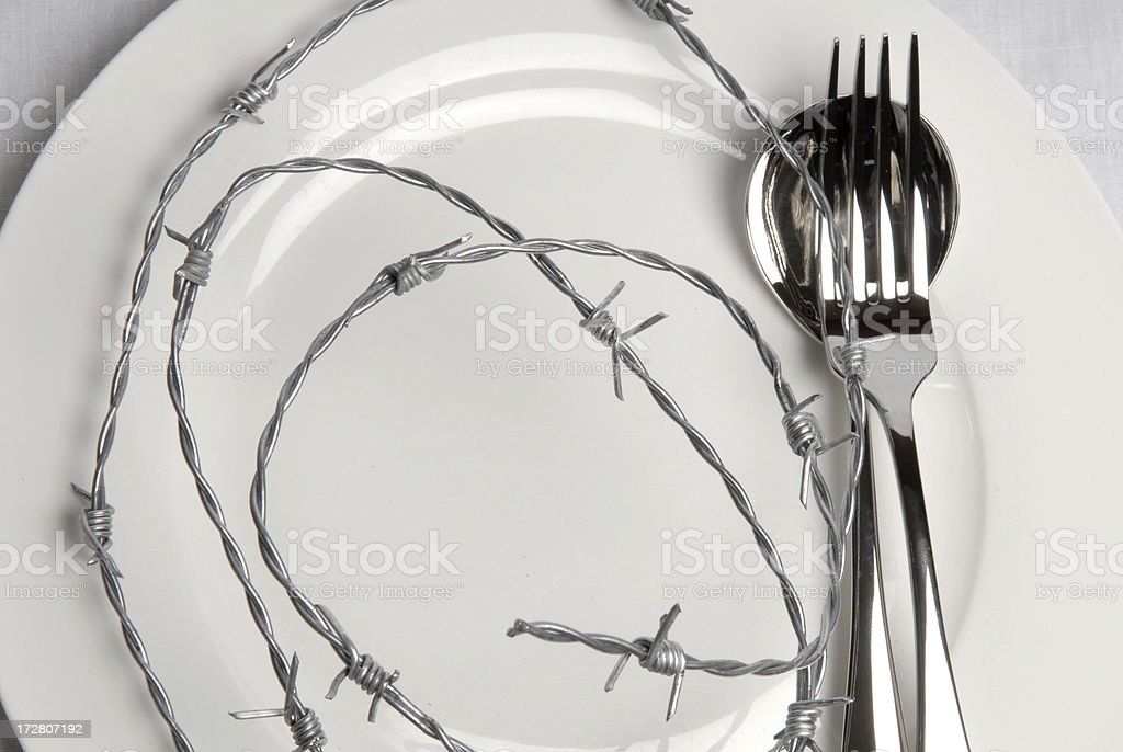 White plate covered in barbed wire - dieting metaphor royalty-free stock photo