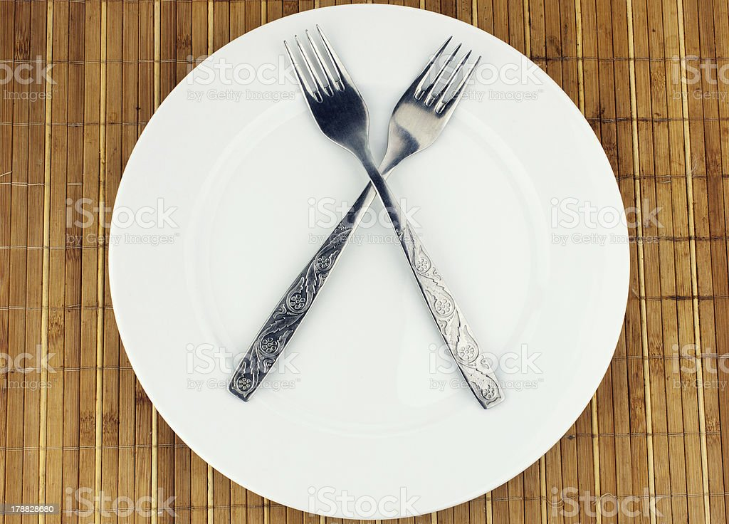 White plate, fork crosswise royalty-free stock photo