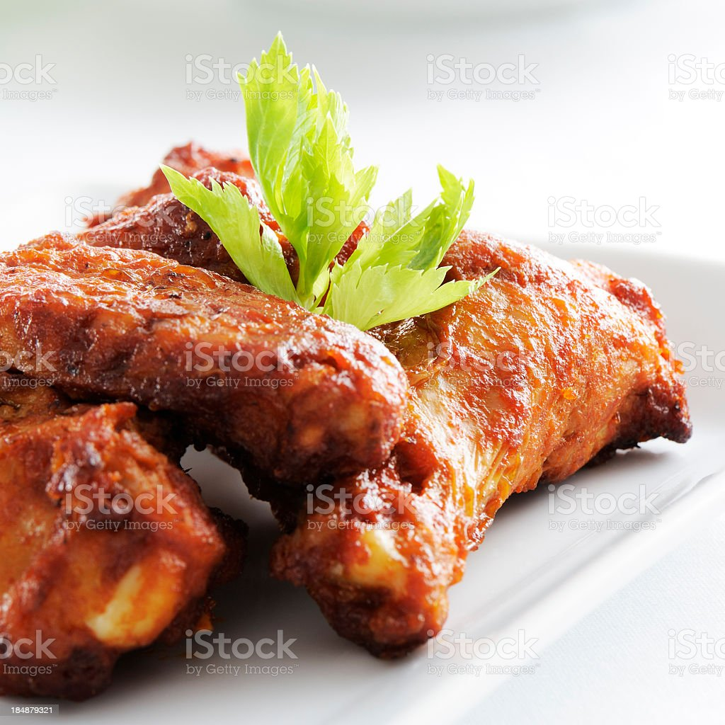 A white plate full of spicy chicken wings stock photo