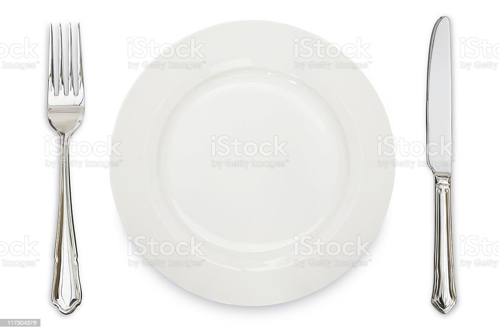 A white plate, knife and fork against a white background royalty-free stock photo