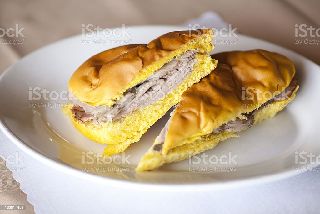 White plate with a Cuban pork sandwich cut in half on it stock photo