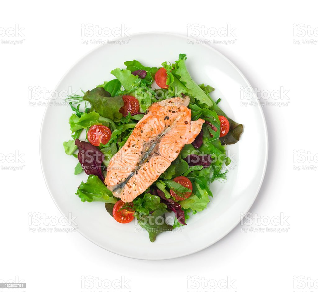 White plate with a salmon filet and green salad stock photo