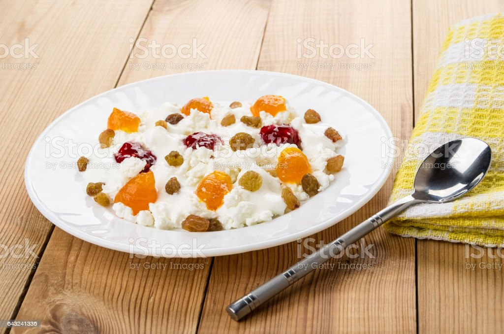 White plate with cottage cheese, yogurt, raisins and different jams stock photo