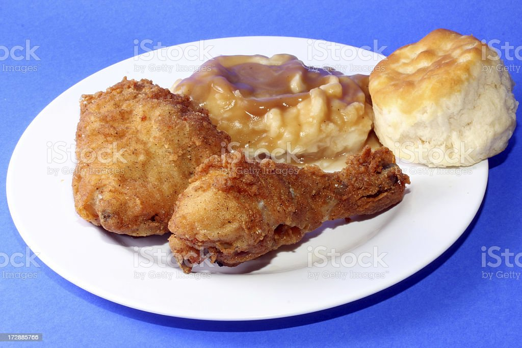White plate with fried chicken breast and thigh, biscuit, mashed potatoes and gravy royalty-free stock photo