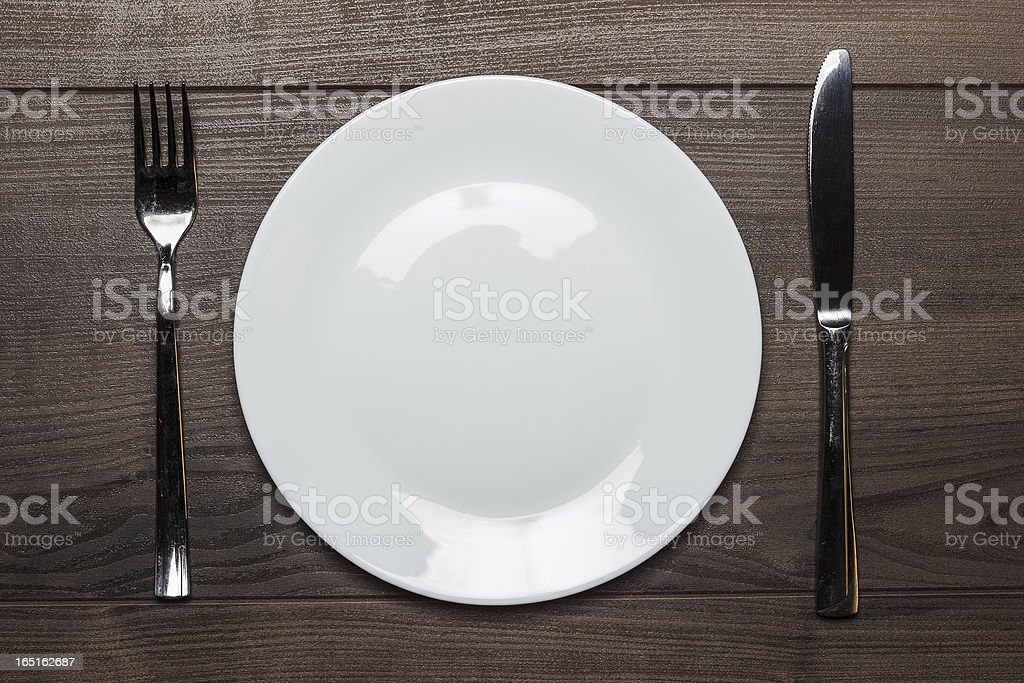 white plate with knife and fork on wooden table royalty-free stock photo
