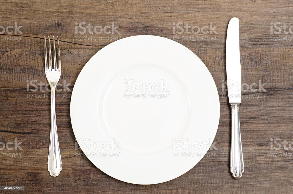 White plate with silver knife and fork stock photo