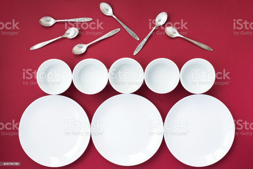 White plates, bowls and silver tea spoons on red background stock photo