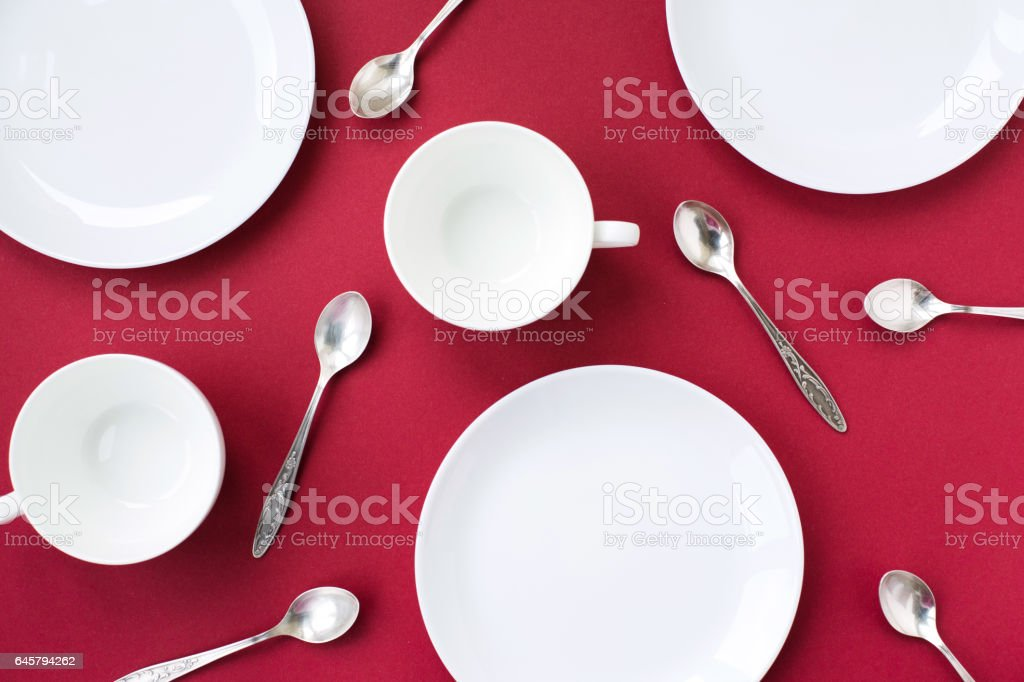 White plates, cups and tea spoons on red background stock photo