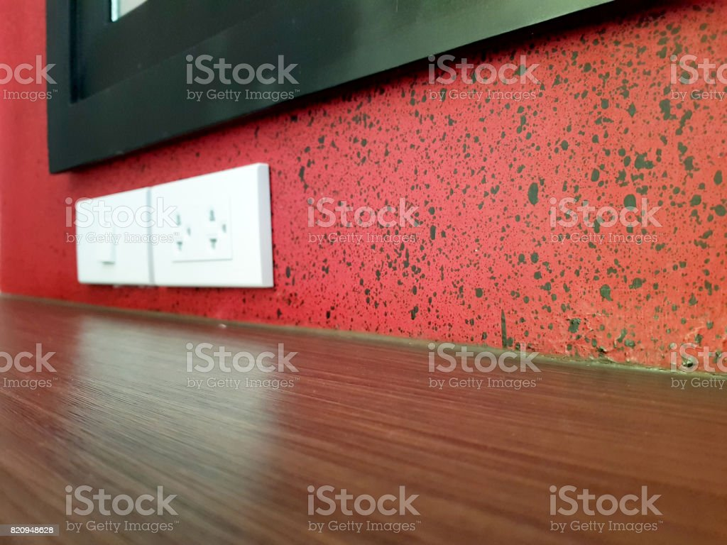White plugs and power switch on red wall stock photo