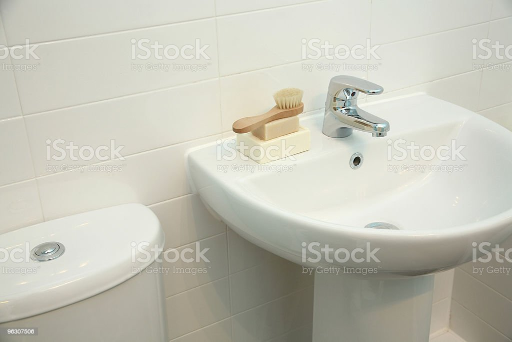 White, porcelain bathroom sink with soap and brush on ledge stock photo