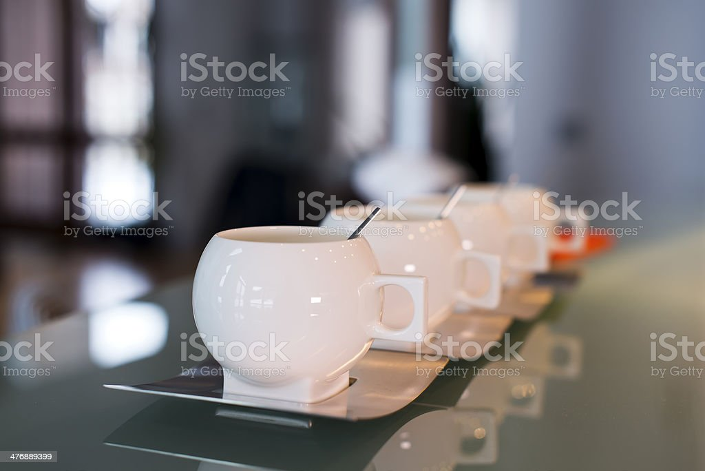 White porcelain modern cups with stainless steel saucers and spoons royalty-free stock photo