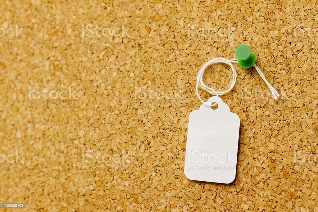 White price tag with string hang on a cork board. stock photo