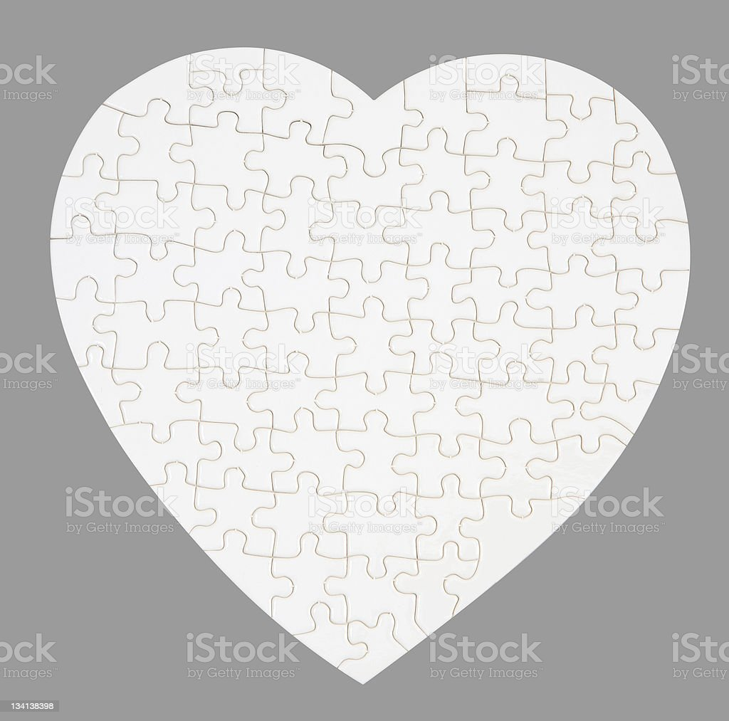 White puzzle heart isolated on gray stock photo