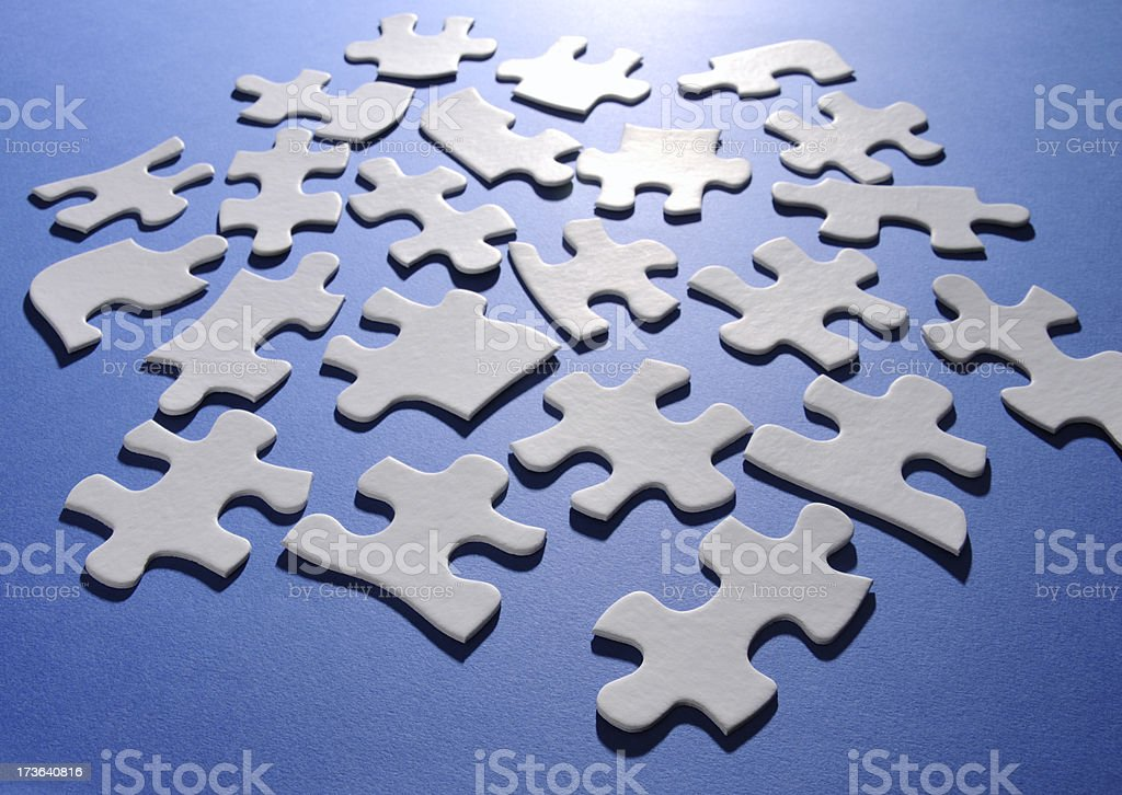 White Puzzle Pieces on Blue Background; Puzzling, Clueless, Difficult, Unresolved stock photo