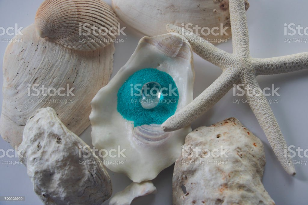 A white quartz stone in a bed of aqua pebbles surrounded by white seashells. stock photo