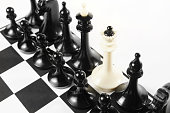White queen between set of black chess pieces