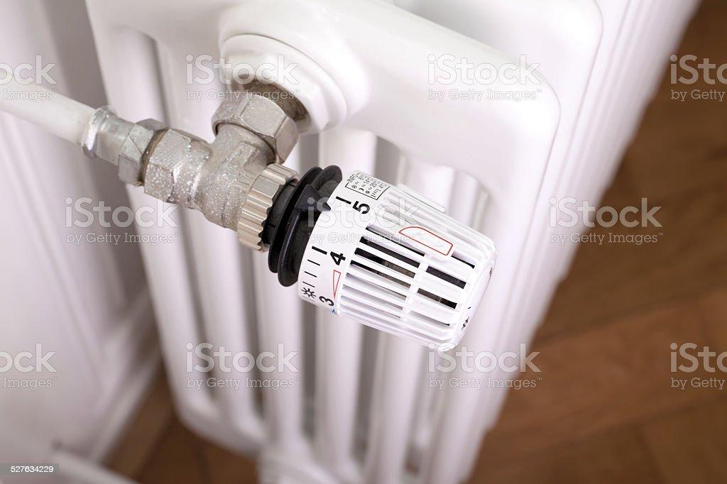 White radiator with white thermostat stock photo