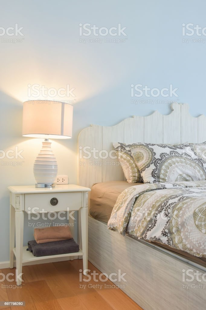 White reading lamp next to modern country style bedding