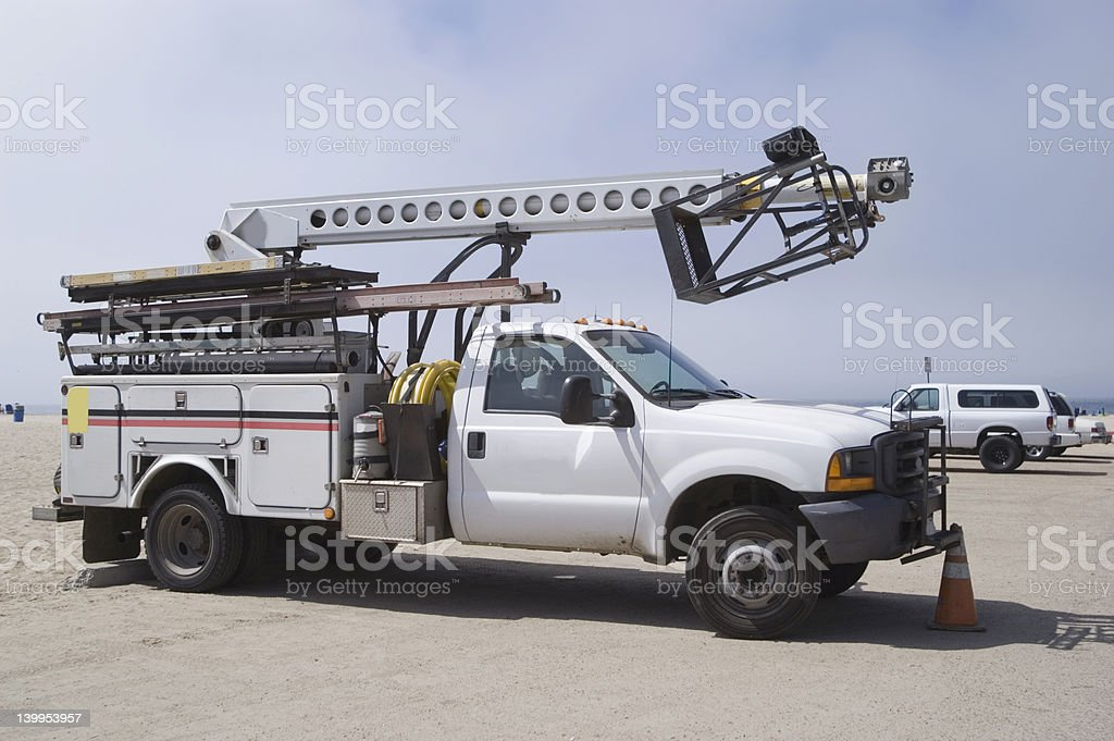 White repair truck carrying a lift in a beach parking lot royalty-free stock photo