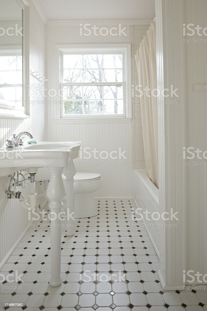 White residential bathroom with tile floor. royalty-free stock photo