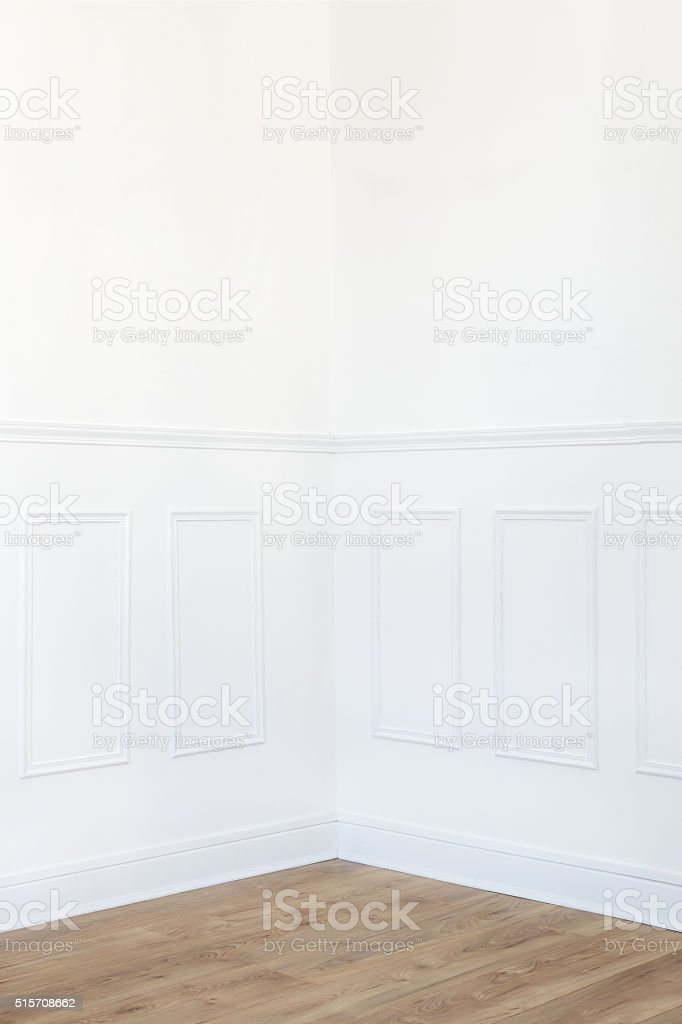 White room corner with parquet floor and wood trimmed wall stock photo