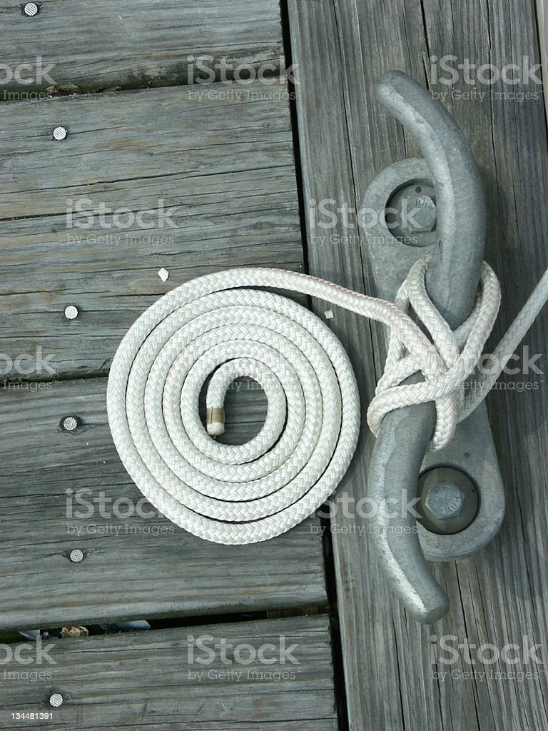 White Rope Coiled on Wooden Dock stock photo