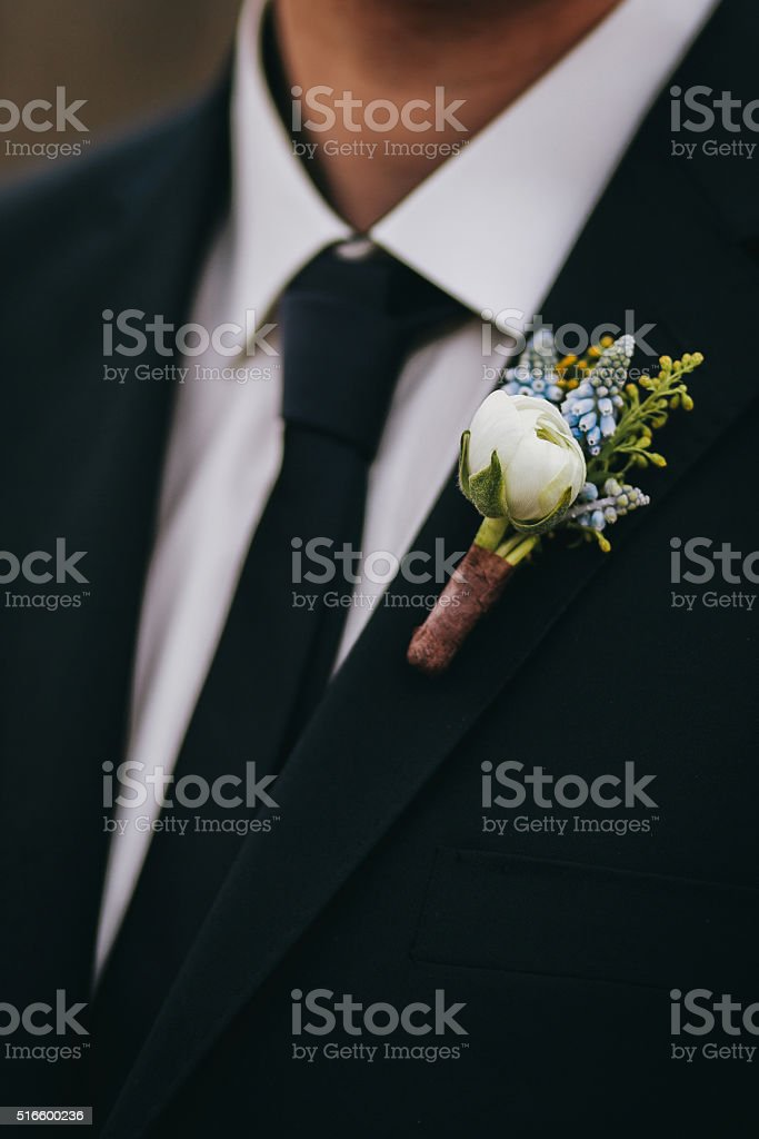 White rose and blue flowers boutonniere on groom's stock photo