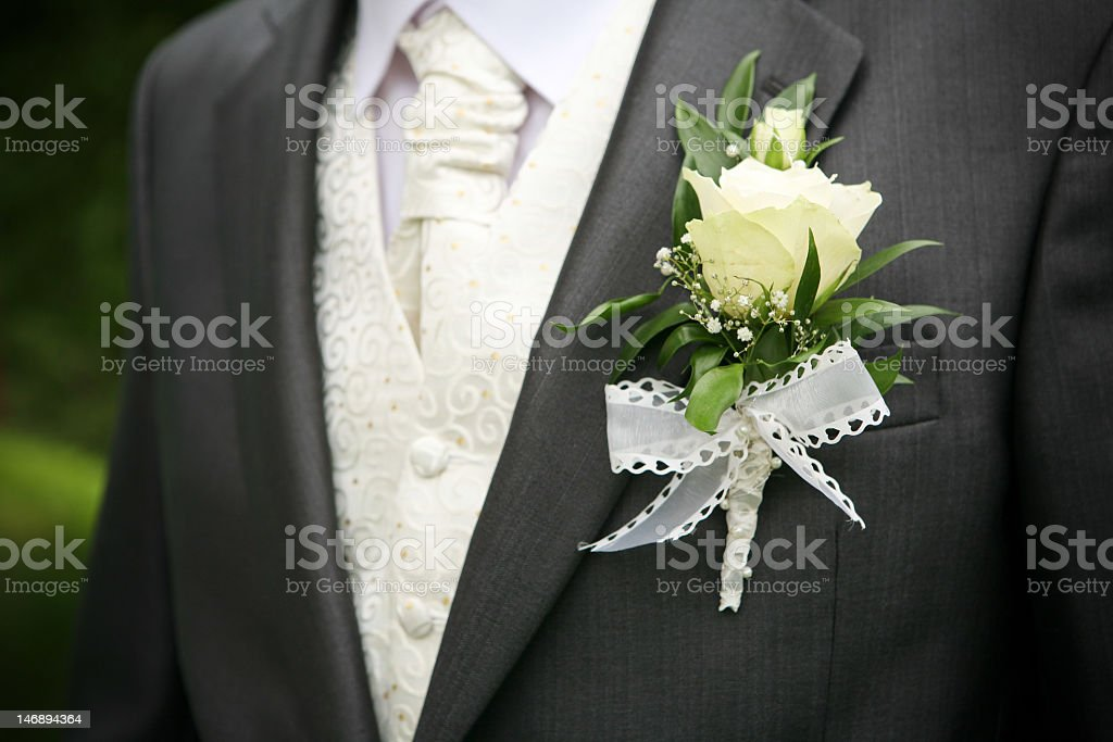 White rose boutonniere on groom's suit stock photo