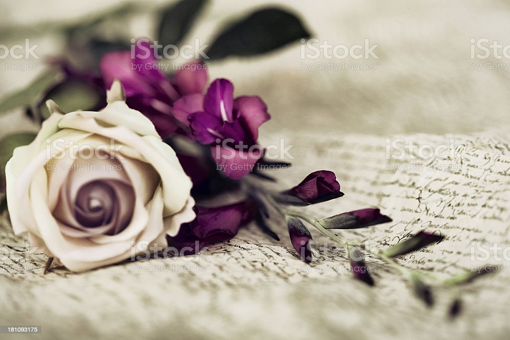 White rose next to purple flowers over a calligraphy cloth royalty-free stock photo