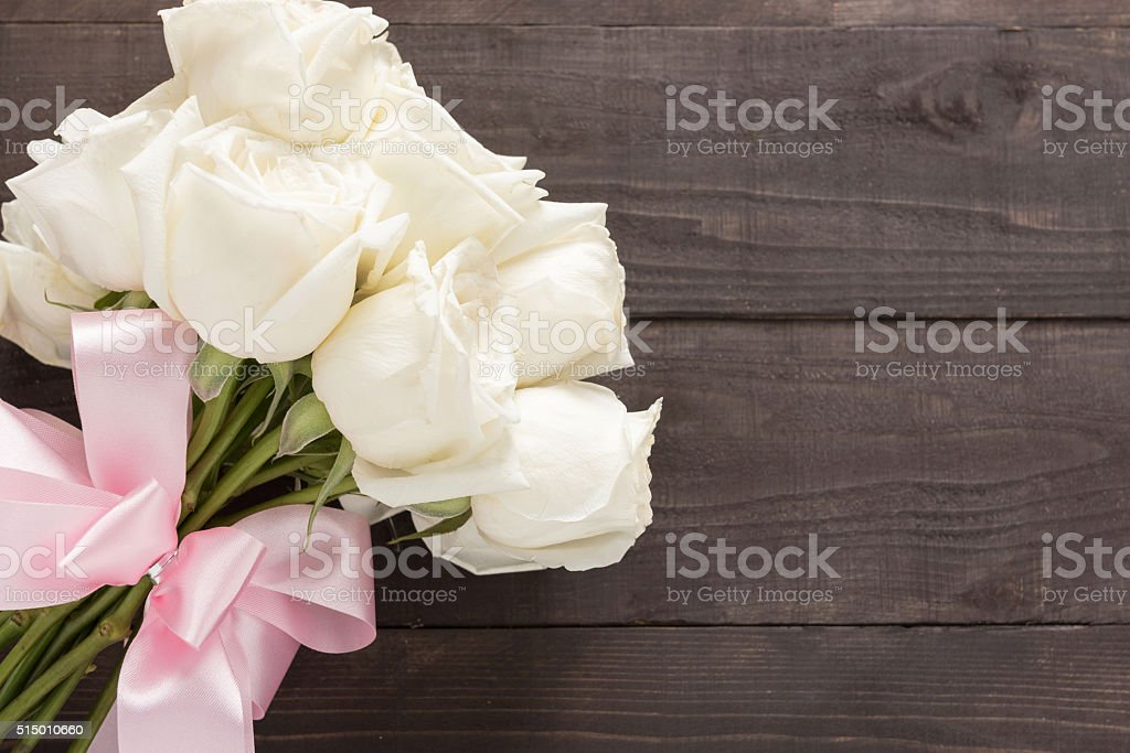 White roses bouquet is on the wooden background with ribbon. stock photo