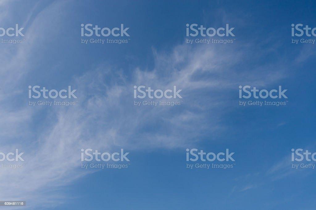 White round cloud, shaped like feather, on blue sky. stock photo