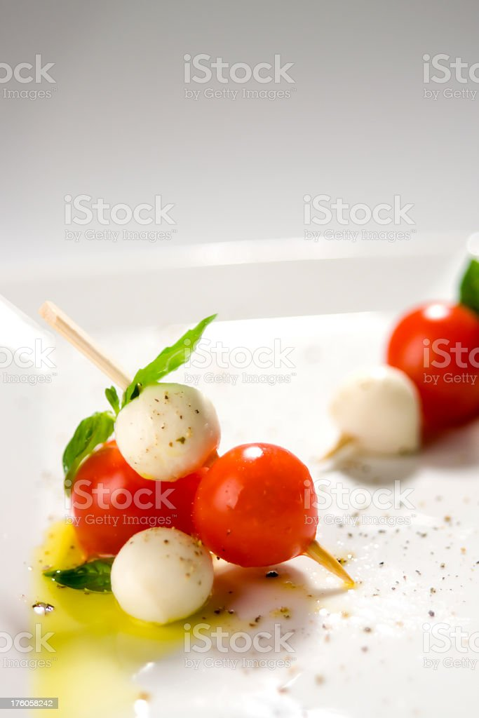 A white round plate with tapas served with tomatoes royalty-free stock photo