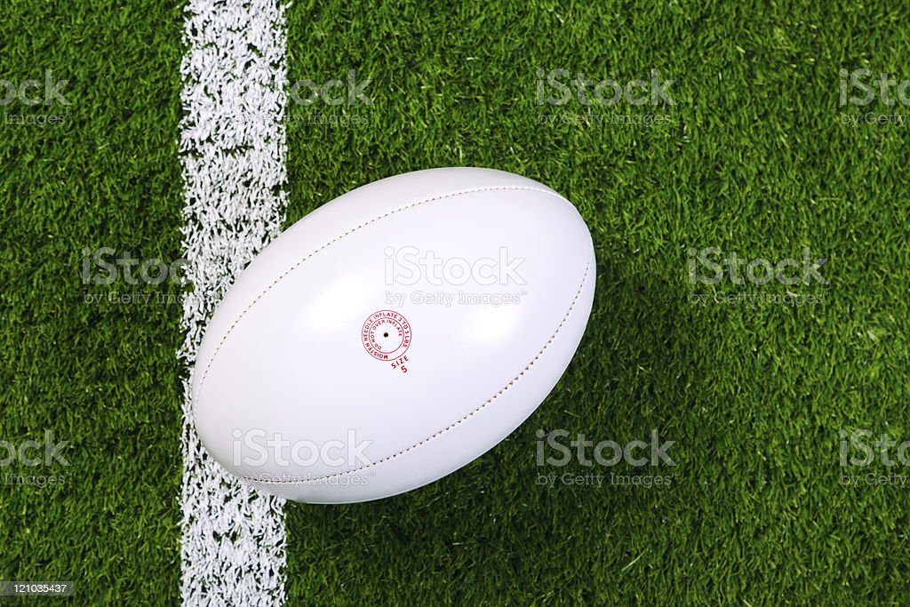 White rugby ball in a grass field shot from above stock photo